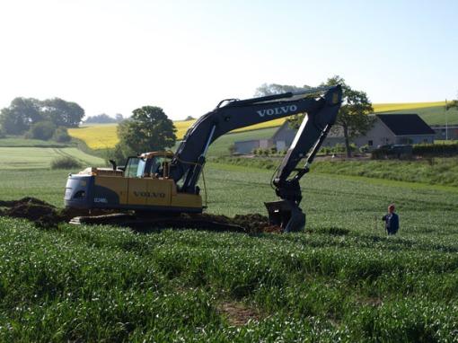 Arkæolog Kirsten Nellemann Nielsen overvåger gravemaskinens fremdrift i én af søgegrøfterne ved Mollerup