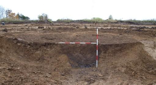 Profilsnit gennem brønd, flankeret af to lertagningsgruber