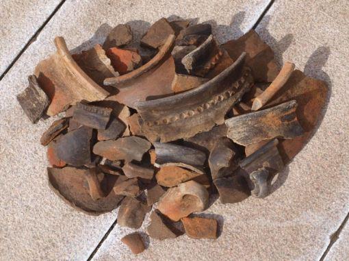 Samling af lerkarskår: sideskår, randskår med dekorative lister, hanke, bunde...