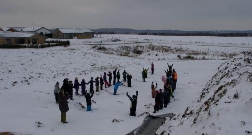 Elever fra Grauballe Skoles 1.-2. klasse tegner et langhus i sneen.