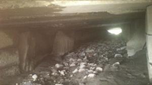 Kig ind i en stenkiste, der er blevet forlænget med beton.